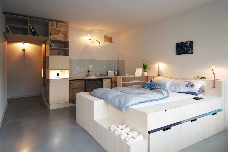 кровать на подиуме в кухне-спальне