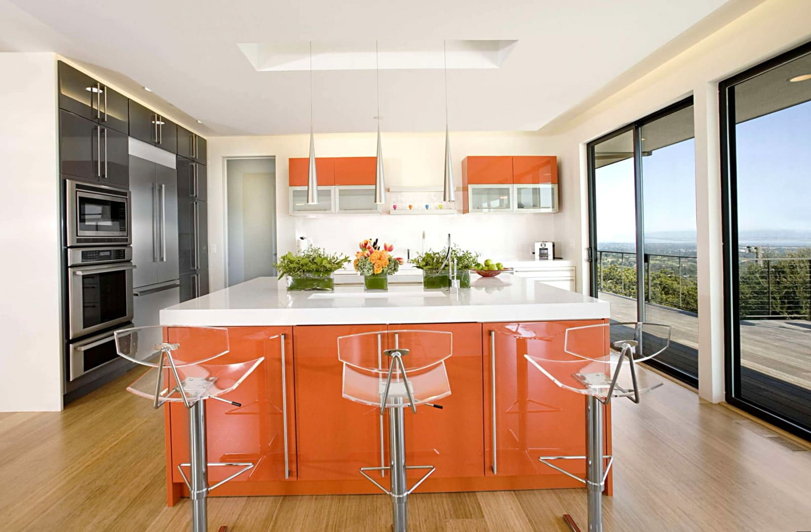 стеклянные стулья в интерьере оранжевой кухни