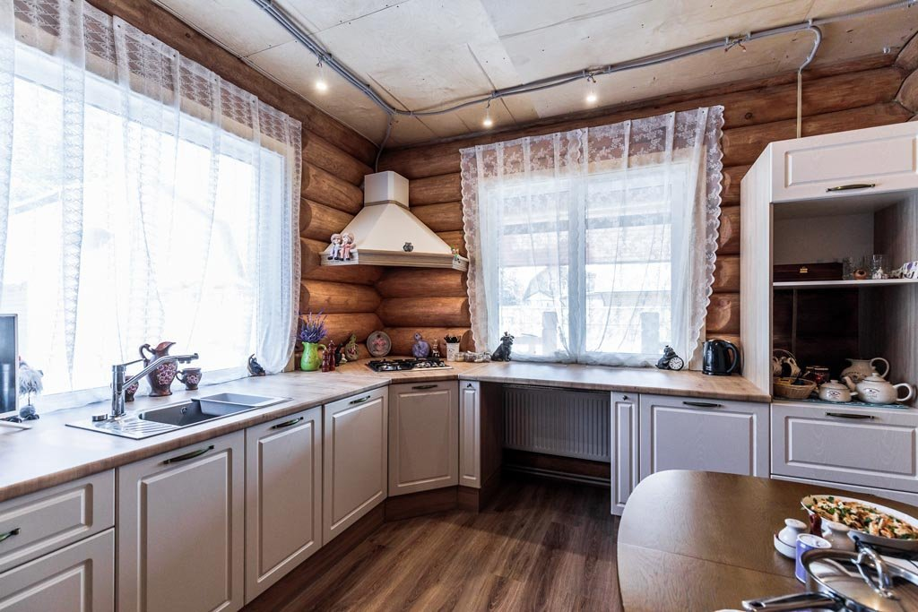 два больших окна в центре кухни в деревянном доме