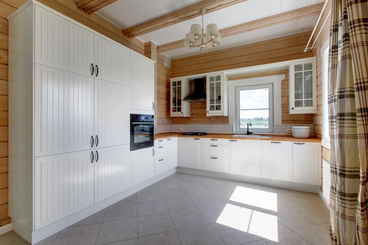 высокая белая кухня в деревянном доме