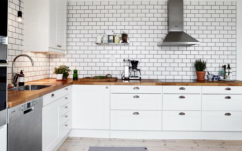 приятный интерьер кухни с белым фартуком