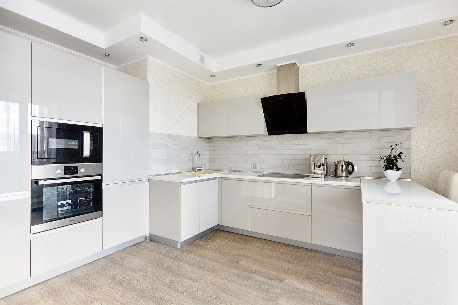 Белая глянцевая кухня без ручек визуально расширяет пространство