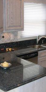 Чёрный гранит на светло-серой кухне